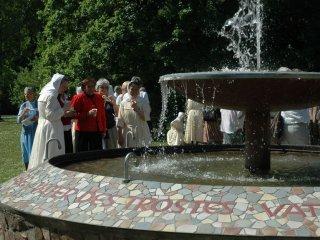 '아버지의 샘'물을 마셔보는 자매들과 방문객들